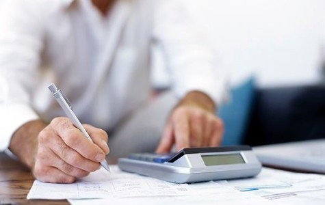 An image of a business owner drawing up and balancing a budget for his company's upcoming fiscal year.