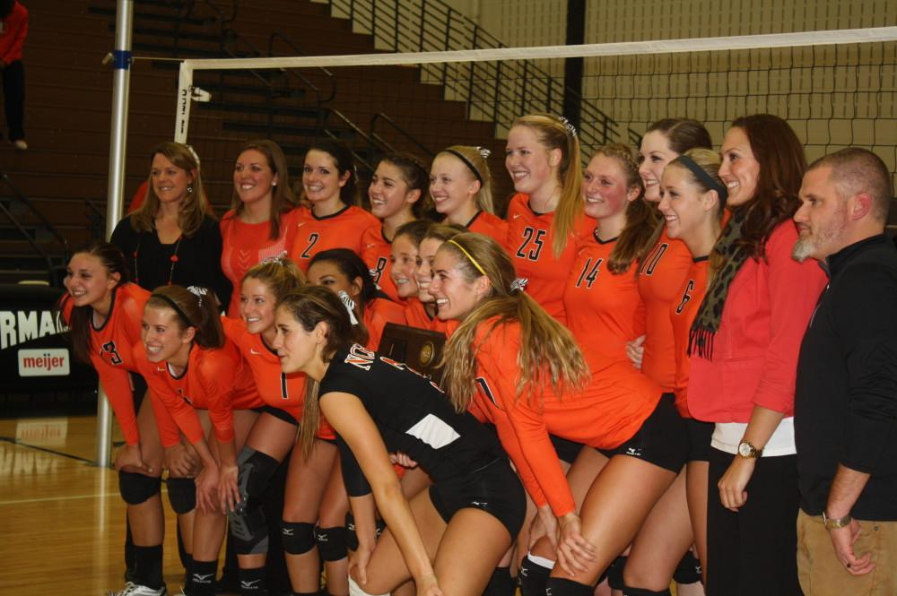 The varsity volleyball team pose as the fans snap a picture of the winning team.