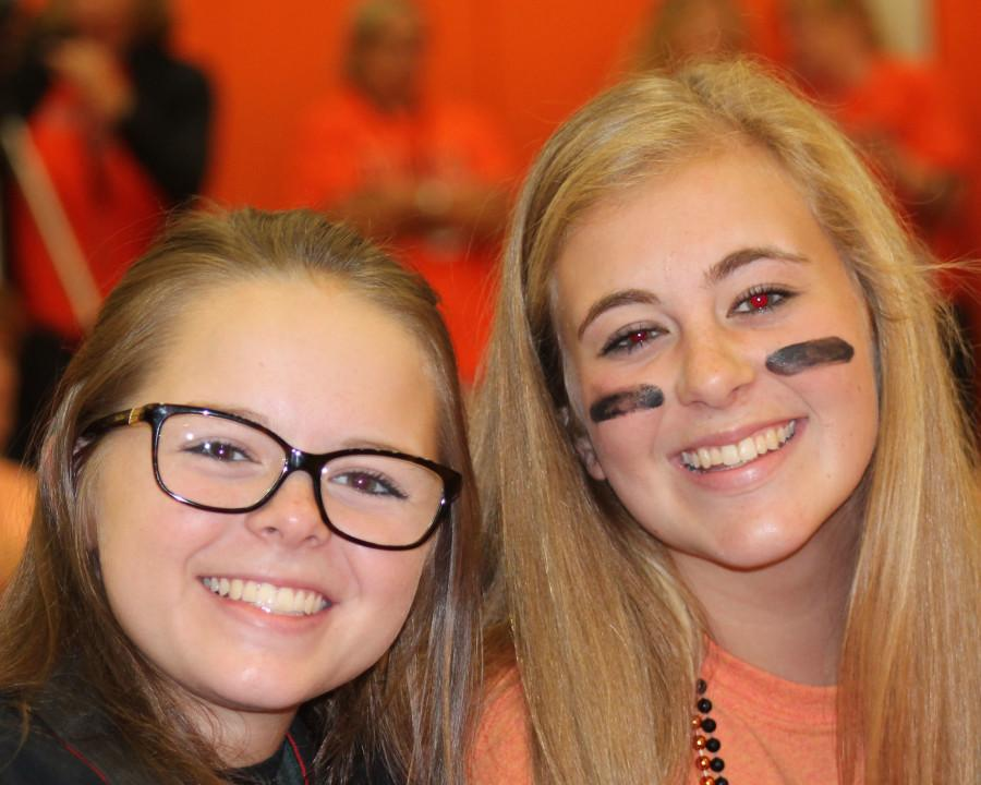 Abby Daneberger (11) and Becca Merrill (11) at the homecoming assembly taking pictures for Yearbook and Journalism.