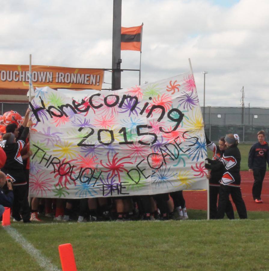 Football players all gather up behind the homecoming sign they will be running through with the cheerleaders to cheer them on.