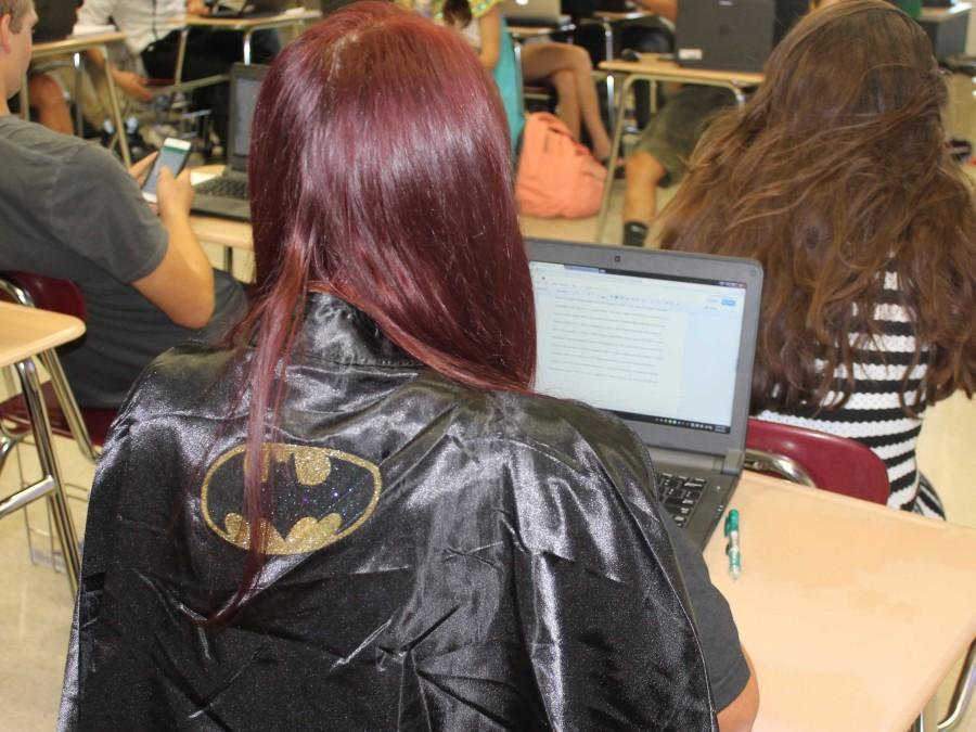 Courtnee Madsen (12) works on her laptop while dressed as Batman.