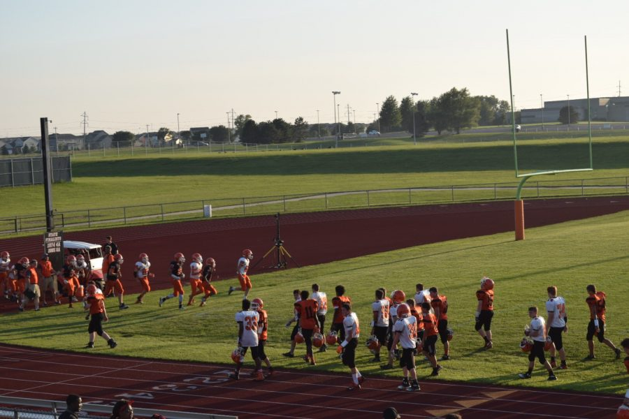 Freshman football players exit the field while sophomore players run on in preparation to play.