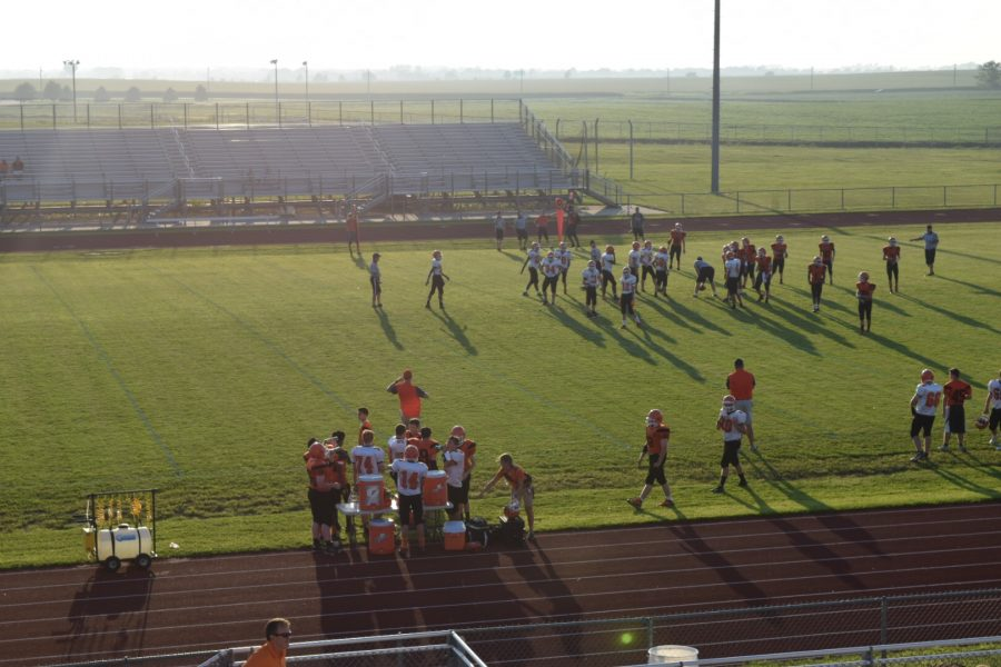 As the scrimmage finishes, players stop to get a drink as they exit the field.