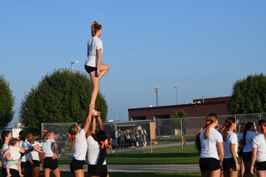 Varsity cheerleaders warm-up before the varsity scrimmage.  Reagan Volz (11) performs a stunt.