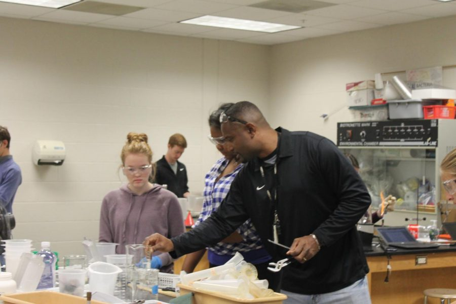 Dr. Walker helps guide his students as they go through a lab.