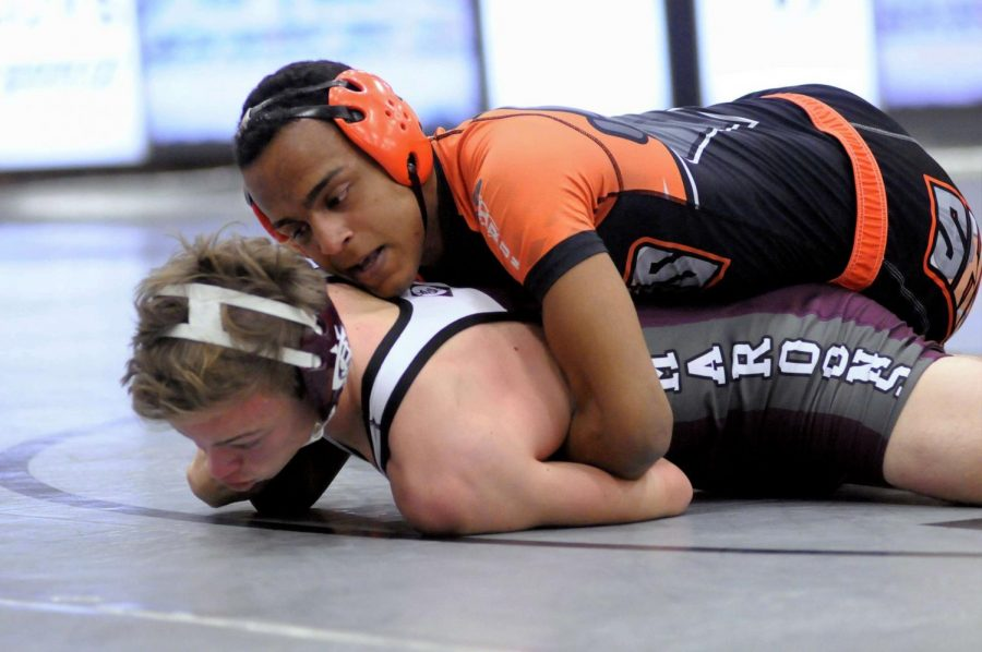 Josh Delgadillo ('19) attempts to transition into a half nelson to pin his opponent from Champaign Central.