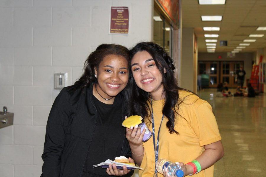 Students pose for a picture with food from the Speakeasy.
