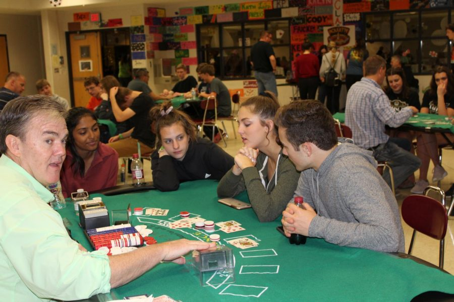 Students playing poker with a parent volunteer to give the students tips and tricks on poker playing strategy.