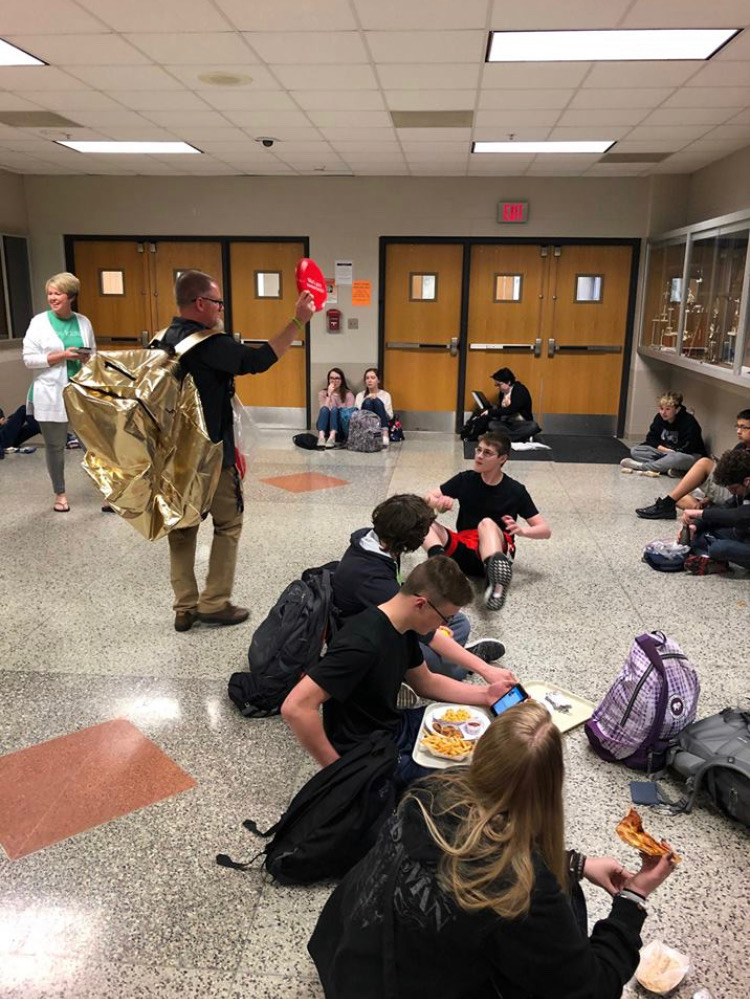 Mr. Jason Ruyle wears an oversized gold backpack while passing out water bottles, frisbees and t-shirts to students.