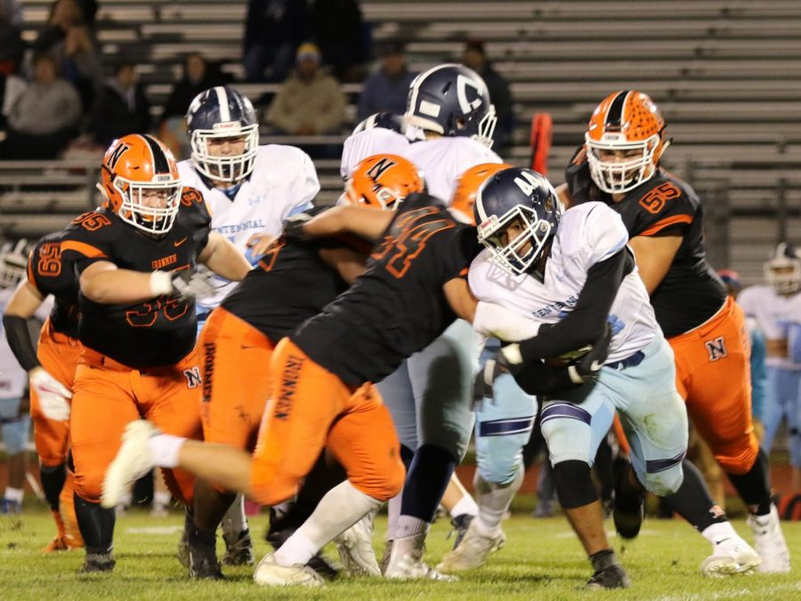 Levi Smaling (44) and a host of Ironmen meet the Centennial ball carrier in the backfield for a tackle for a loss.