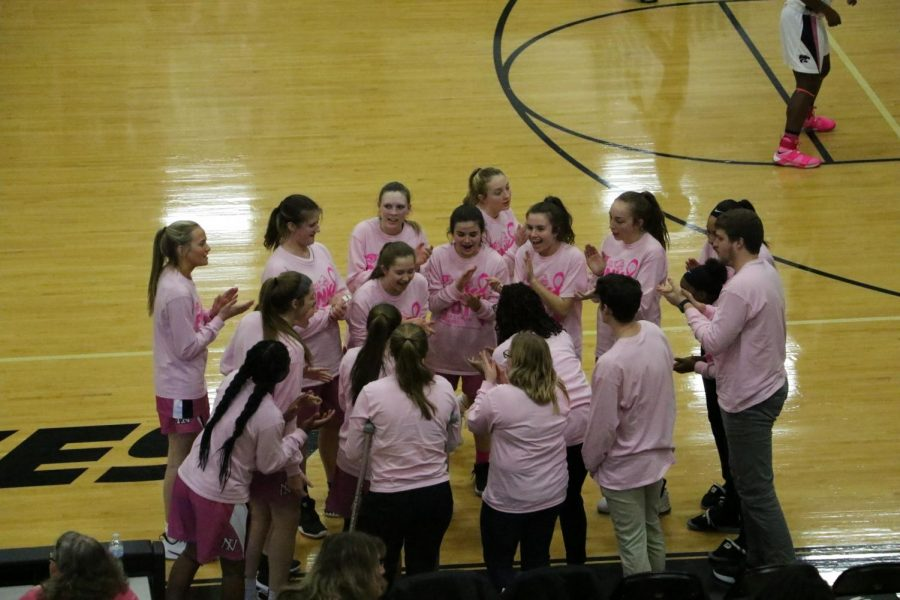 The Lady Iron varsity basketball team huddles before their annual Pink Game versus Normal West. The Wildcats won 45-26.