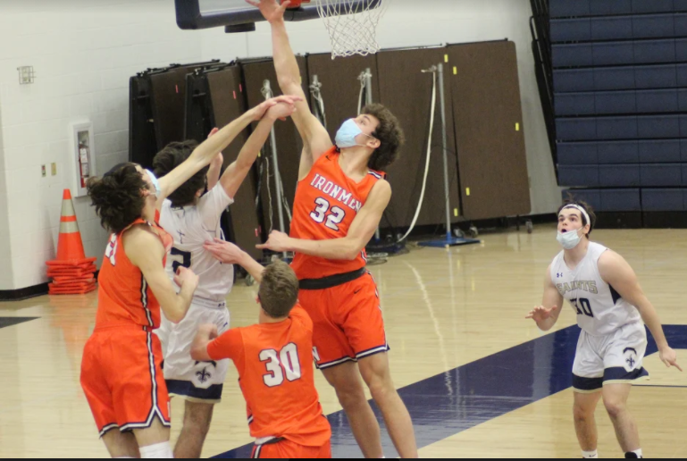 Zach Cleveland ('22) and Jacob Janssen ('21) attempt to block a shot in a game against Central Catholic earlier this season.  Strong interior defense helped the Ironmen hold Peoria High 11 points below their season average.