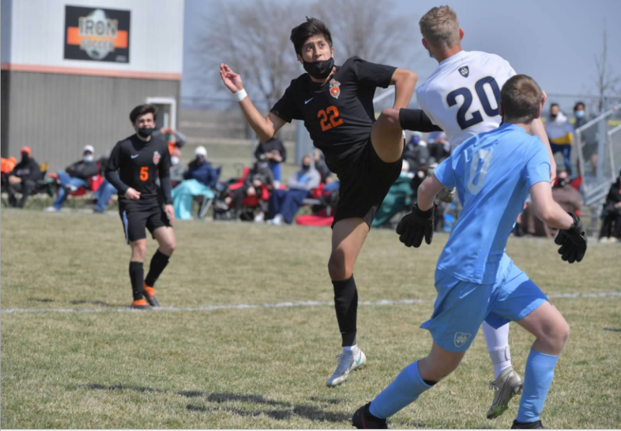 Castaneda battles for the ball in a game against Quincy Notre Dame last season. This is his third year playing varsity soccer for the Ironmen.